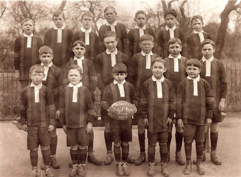 <b>Meldreth School Rugby Team, 1925</b><br> From the school log book on 10th March 1925:<br> Mr M Mitchell of Christ's College Cambridge has offered to teach the boys of the school Australian Rugby Football.  He has also offered to buy their equipment.  His offer has been accepted.<br> Back row, from left: Horace (Sonny) Waldock, Ken Farnham, Archie Jacklin, Norman Gipson, Theo Mead, Cecil Handscombe, Jackie Dossett<br> Middle row, from left: Harry Pepper, William (Bill) Thurley, Eric Nodder, Sid Pearce, Albert Green, Bill Dossett<br> Front row, from left: Alfred Mead, Albert Walbey, Donald East, Sidney Butler, Rosslyn Nodder<br> | Photograph supplied by Ann Handscombe