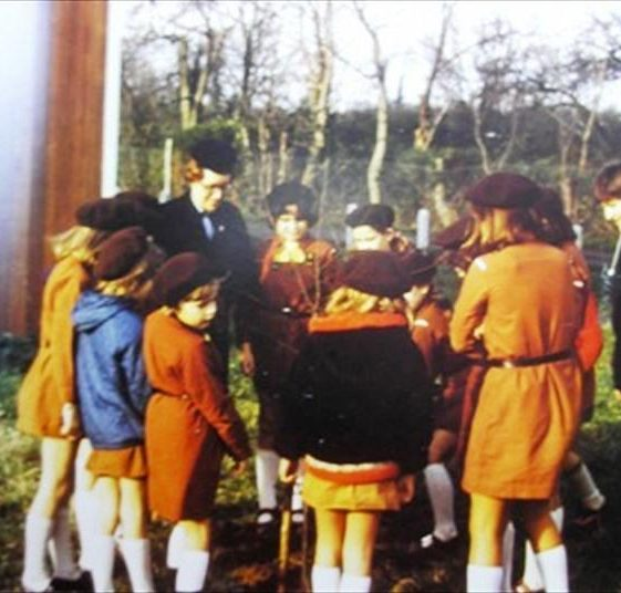 Mrs Ann Handscombe with Brownies planing a tree outside the Village Hall, corner of Elin Way and High Street, Meldreth.  1974 | Photo supplied by Meldreth W.I.