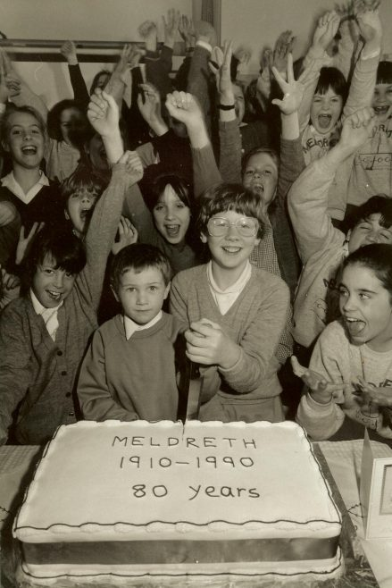The youngest pupil, four year old Steven McGill and the oldest, Rebecca Reed, cut the 80th birthday cake | Photograph courtesy of Meldreth Primary School