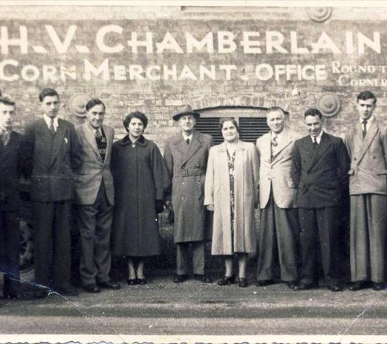 Group of employees outside H.V. Chamberlain, High Street, Meldreth. 1953. l/r Sarah Butler, Peter Oakman, John Thompson, Harold Hinkins, Ann Carter, H.V. Chamberlain, Maggie Green, Tom Thurley, Geoff Warboys, Colin Salmon, Brian Mayo. | Photo supplied by Tim Gane