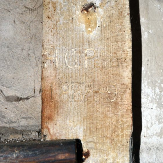 Ground floor: H G Peters' initials carved in beam, with the dates 1887-1897.  Herbert Peters' family operated the mill during this period; there is a photograph of them on the other Topcliffe Mill picture gallery on this site.  December 2013. | Photograph by Kathryn Betts