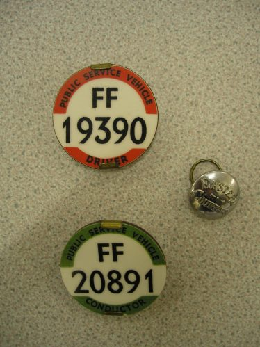 Bus Driver and Conductor's badges from the 108 Bus. | Photo by Tim Gane, courtesy of Joan Fallon.  Joan's husband, John, worked on the 108 bus.