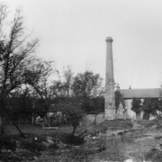 Flambards Mill after the fire.  Only the chimney and wheel housing remain.  The farmhouse can be seen in the background.