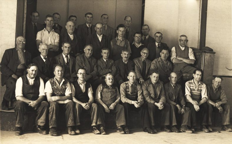 Group of Atlas Workers in March 1955<br> Back Row L to R: ____, _____, _____, _____, Fred Billett, Reg Catley<br> Third Row L to R: Harry Pullen, ____, _____, Jack Catley, _____Stan Watts, Bob Woods, _____.<br> Second Row L to R: George Pullen, ____, _____, Ted Day, ____, Bob Smith (blacksmith), Sid Chamberlain, ____ , _____<br> Front Row L to R: Bill Bullen, Charlie Phillips, Alec Newman, _____, ____, ____, ____, Sid Smith, ______. | Christine Keith