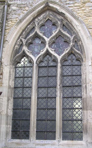 The western window in the north wall of the nave has the same flowing forms as the chancel window but now in a broader window with three lights. The flowing forms result from the use of reverse curves (so-called ogee arches) at the head of each lancet.   Peter Draper