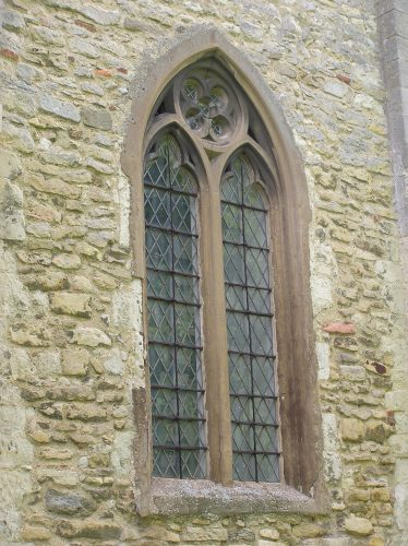 The opresent window is entirely 19th century but may follow fairly faithfully a late 13thc window which must have been inserted into the west face of the tower when the upper stage was built. The quatrefoil is now enclosed within a circle and the bars of stone have become thinner. | Peter Draper