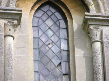 Water-leaf capitals. with the typical upward curl at the end of the leaf, on this window inserted in the 19th century into the second stage of the tower | Peter Draper