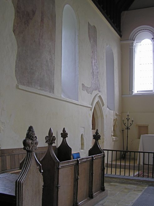 Chancel showing 15thc stalls, 14thc blocked door to former vestry, piscina and aumbry, and wall paintings | Peter Draper