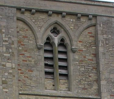 The two-light window with a quatrefoil above in the upper stage of the tower marks the beginning of patterns in stone to decorate window openings. The steeply-pointed profile of the arch and cusped heads to the lancets are typical of the later 13th century. The window has been completely rebuilt during restoration in the 1960s. | Peter Draper