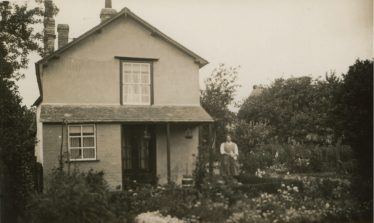 Photograph 8: The Jacklin House stood end on to Chiswick End.  Dolly Jacklin (nee Wing) is standing in the garden.  The edge of the Chiswick Farm Cottages is just visible over the trees. c. 1928 | Bill Wing