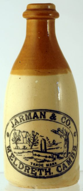 JARMAN & CO GINGER BEER BOTTLE. 7ins tall, ch. t.t. 'JARMAN & CO/ MELDRETH CAMBS' village stocks scene pictured. Tiny insignificant inside rim flake, & 1 to base. Extremely rare. NR £120-150+. | Advertised for sale on BBRA Collectors Mart Auction website,Saturday 2nd and Sunday 3rd October 2010