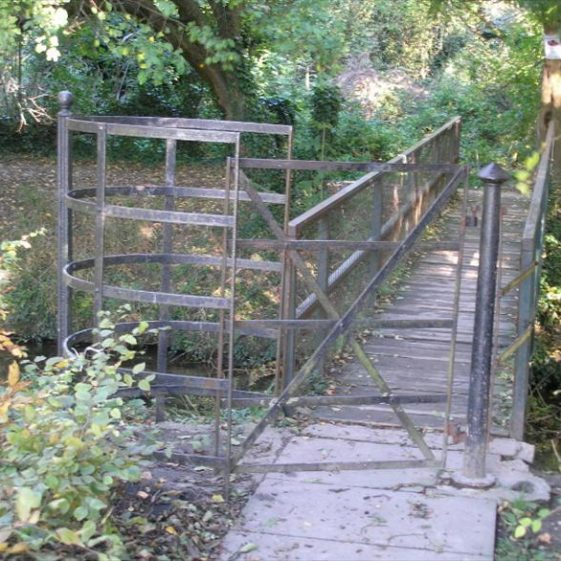 The kissing gate on the bridge over the River Mel into Melwood.  Inscription cast on gate post reads: RAWLINGS MOOR END WORKS, MELBOURN 1862.  It was moved from the footpath near Cowslip corner following construction of the bypass in the 1980s. | Photograph by Tim Gane