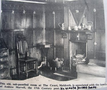 Newspaper cutting showing the interior of the study in Meldreth Court with the panelling and the 'AM' Andrew Marvell mirror | 1965 Women's Institute scrapbook.  The origin of the newspaper cutting is  not known