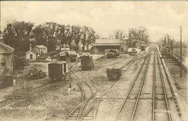 Photograph of the Goods Yard at Meldreth Station ~1925 - 35.  The large warehouse is on the extreme left of the photograph. | Postcard, photo by J Bishop