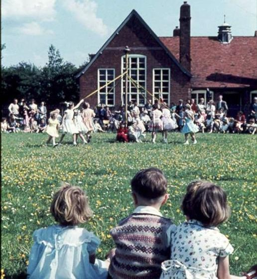 Children at Meldreth School, High Street, Meldreth during May Day celebrations.  Keith Saunders, Julie and Elaine Handscombe are in the foreground.  1961 | Photo supplied by Ann Handscombe