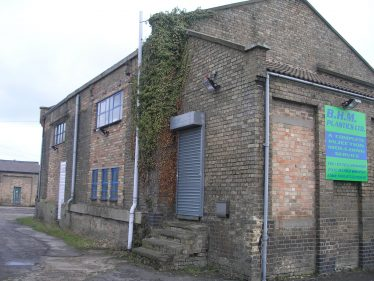 The Warehouse in 2010.  The door and window in the office have been bricked up.  The awning has gone as have the large sliding doors.  The openings have been bricked up.  Note the old stables in the background. | Tim Gane
