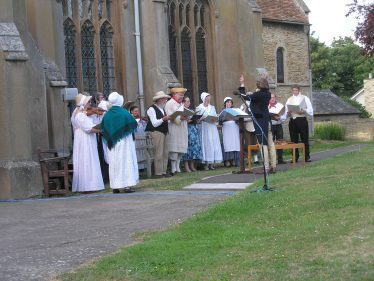 The Chiltern West Gallery Quire performing psalms and anthems from the Meldreth Psalm Book in Holy Trinity Churchyard on July 9th 2009 | Tim Gane