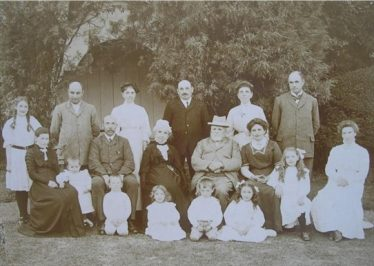 The Palmer family shown outside the summer house in Old Elmcroft, Meldreth c.1909. William Palmer is thought to be the tall figure standing in the back row on the right. | Photo courtesy of Robert Elbourn