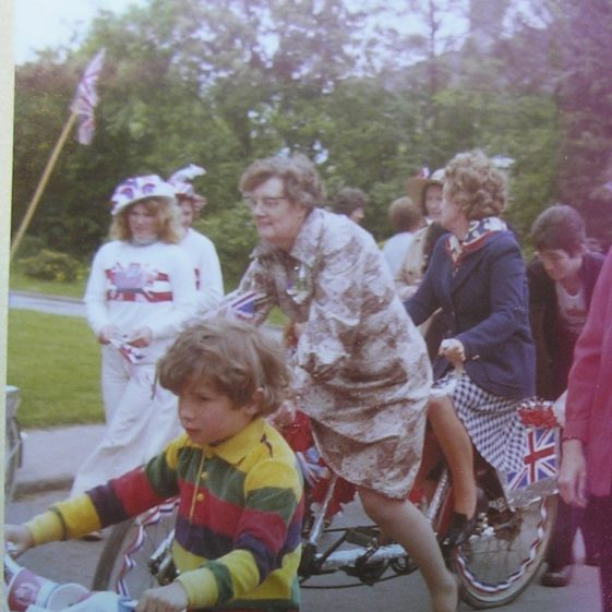 Chairman of the Parish Council Mrs Mary Course and Mrs Joan Gipson lead the parade on their bicycle made for two | W.I Scrapbook 1977