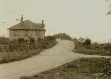 The Station House on the end of the Large Warehouse on Station Hill ~1920 - 30.  The gable for hoisting the sacks of coprolite is clearly visible.  The vanes of the wind pump can just be seen to the left of the chimney.  The line for Puffing Billy can also be seen crossing the road and entering the goods yard via a 5 bar gate. | Bells Postcard