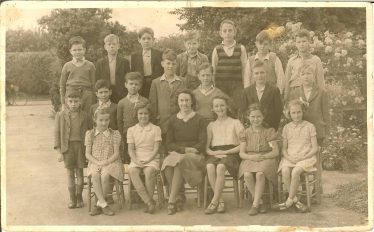 Class 2 of Meldreth School, pictured in 1946.  Ken Winter is second from the right in the back row.  Miss Broughton is in the front row. | Photograph courtesy of Ken Winter